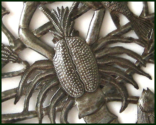 Close-up of Haitian metal art wall hanging.